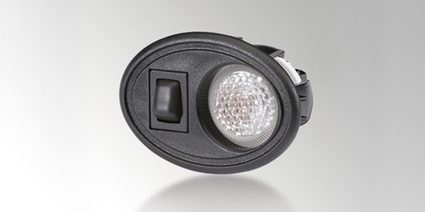 Interior reading spotlight incorporating bulb technology and glass lens, with light and switch integrated into oval housing form, black, by HELLA